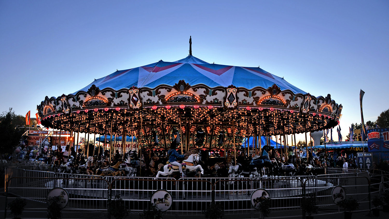 At dusk, children ride a brightly-lit merry-go-round.