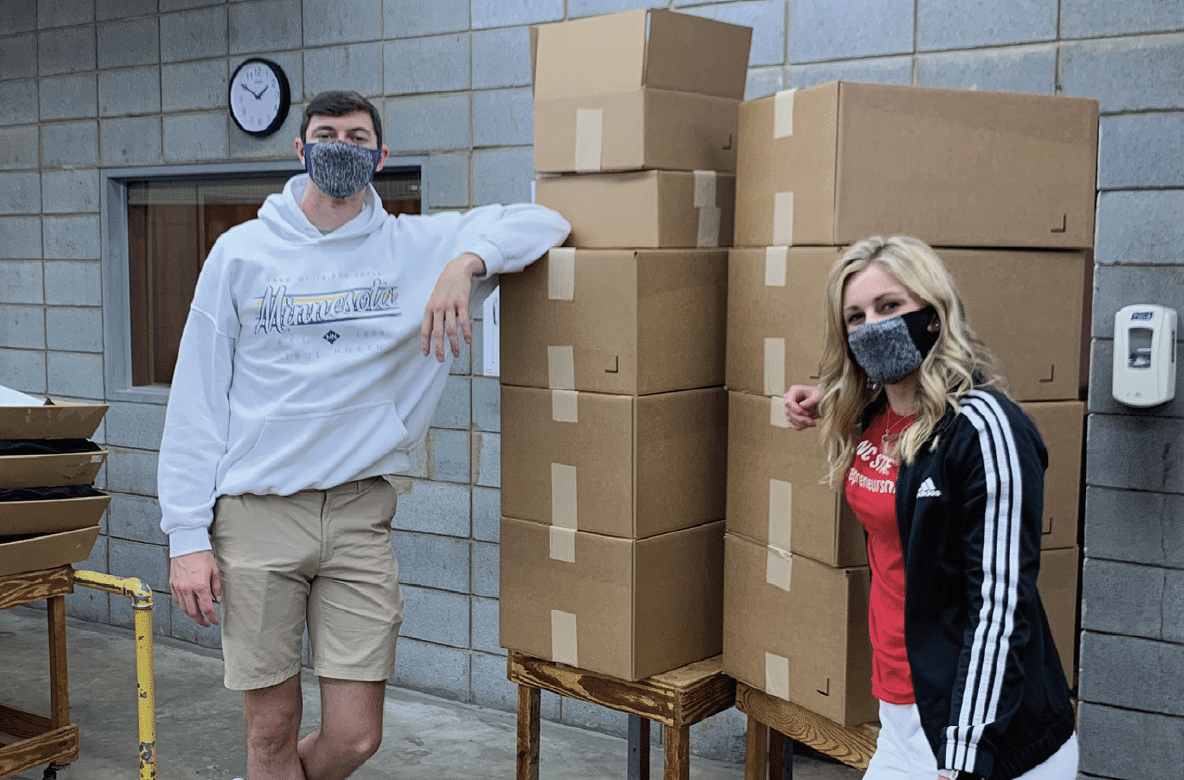Katie Lawson and Eric Swanson stand before a shipment of Easy Masks in April