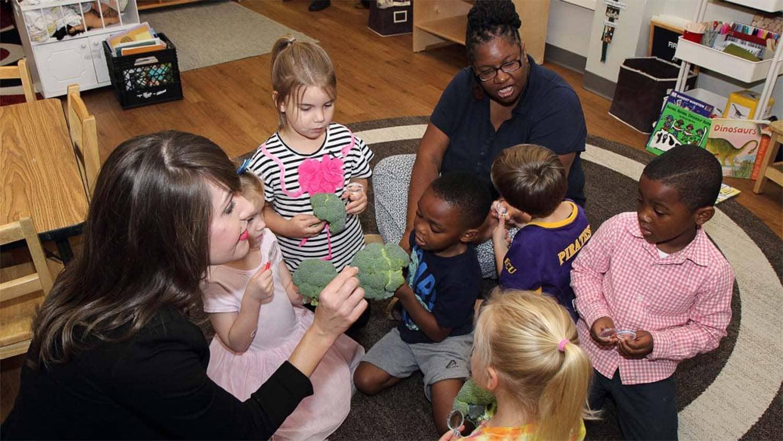 White woman showing broccoli to preschool children